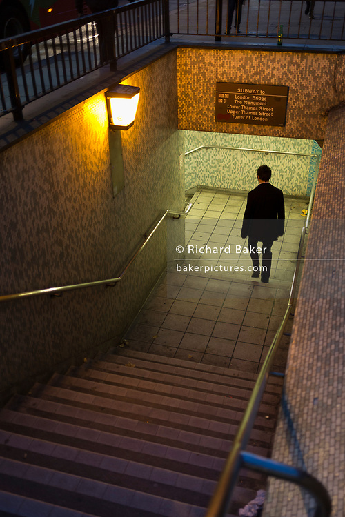 A male pedestrian descends the steps into the tunnel under London Bridge during the evening rush-hour, on 8th November 2018, in London, England.