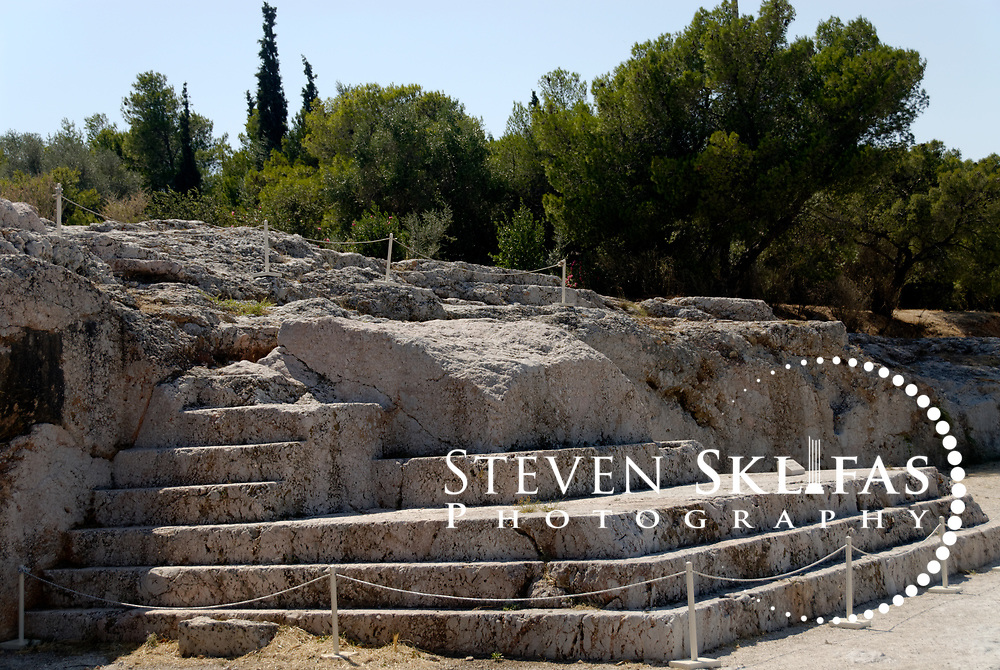 Pnyx Hill. Athens. Greece. View on Pnyx Hill of the bema, the stepped platform carved from the bedrock from which speakers including great statesmen's addressed the citizens Assembly during the 5th and 4th centuries BC.  The Assembly met on the terrace in front of the bema 40 times a year to discuss and vote on proposed legislation and at least 5000 citizens were required to attend each gathering.