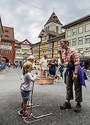 Families blow bubbles on Poststrasse, in Appenzell village, Switzerland, Europe. Frescoes decorate many of the buildings which date from the 1500s. The solid red building in the background is the Rathaus (built 1560-83), which houses the city hall, Appenzell Museum, tourist office and library, on Hauptgasse (Main Street). Appenzell Innerrhoden is Switzerland's most traditional and smallest-population canton (second smallest by area). For licensing options, please inquire.