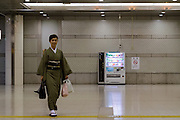 A woman wearing a kimono walks past a vending machine in Tokyo Station, Tokyo, May 29th 2015
