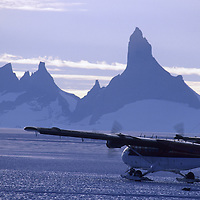 """ANTARCTICA. Twin Otter taxis on bare ice """"Blue One"""" runway in Queen Maud Land. Fenris Mts. & Mt. Ulvetanna bkg."""