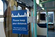 Public transport signs to Please keep your distance as part of social distancing rules on Docklands Light Railway or DLR trains on the day that it was announced that the Coronavirus lockdown measures are set to ease even further and the quiet city starts coming to an end, on 23rd June 2020 in London, England, United Kingdom. As of today the government has relaxed its lockdown rules, and is allowing some non-essential shops to open with individual shops setting up social distancing queueing systems.