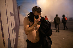 "© Licensed to London News Pictures. 22/01/2020. Beirut, Lebanon. A topless man walks away from tear gas as demonstrators riot on a main highway in Beirut following the announcement late last night that a government has been formed. Police respond with tear gas and water cannon against the anti-government demonstrators. Violence has been escalating in the capital following a ""week of wrath"", where demonstrators were campaigning against government corruption and economic crisis. Photo credit : Tom Nicholson/LNP"