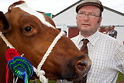 Martin Wall shows off his prize winning heifer. The hairdryers are out and the shampoo is flowing at the Great Yorkshire Show, one of Britain's biggest agricultural shows. Its famous for its competitive displays of livestock. The event, established in 1837, attracts over 125 000 visitors a year and has over 10 000 entries to its pedigree competitions ranging from pigeons and rabbits to bulls and shire horses. At the heart of the show is the passion of the exhibitors who spend hundreds of hours ( and pounds)  training, preparing and grooming their animals. As one competitor put it ?I'm proud to say that the cattle are my friend, I have had cattle who have died and I have sat down and wept for them?