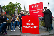 Tourists look on as a man holds a sign referencing a famous Winston Churchill quote  Courage begrets courage outside  the Houses of Parliament on 9th September 2019 in London, United Kingdom. Prime Minister Boris Johnson is tabling another motion to seek a general election.