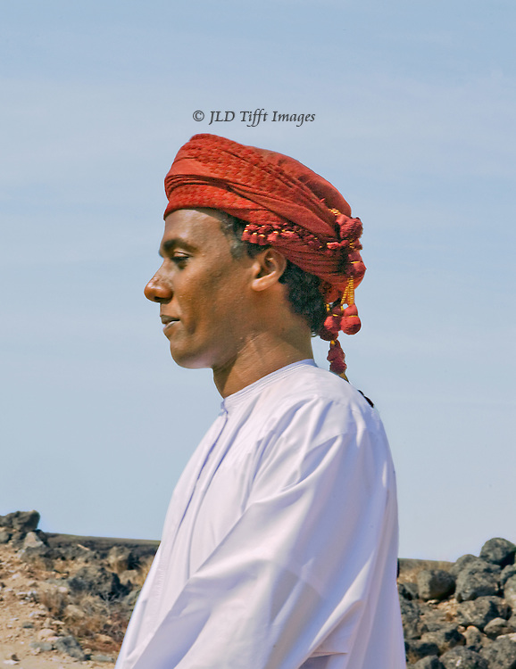 Portrait of an Omani young man in white dishdasha and red turban, seen in profile against a blue sky and distant desert landscape.  He is a guide at the ruins of the ancient port city of Sumhuram, southern Oman.