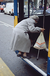 Elderly woman getting onto bus,