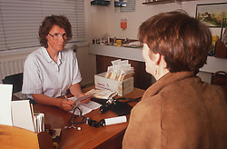 Female doctor talking to patient in GP surgery,