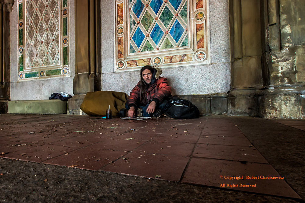 Desperation: A homeless man sits in amongst his few processions;  enveloped in the gloom of despair, to be utterly alone- in a deserted room,  Central Park, New York, New York USA.