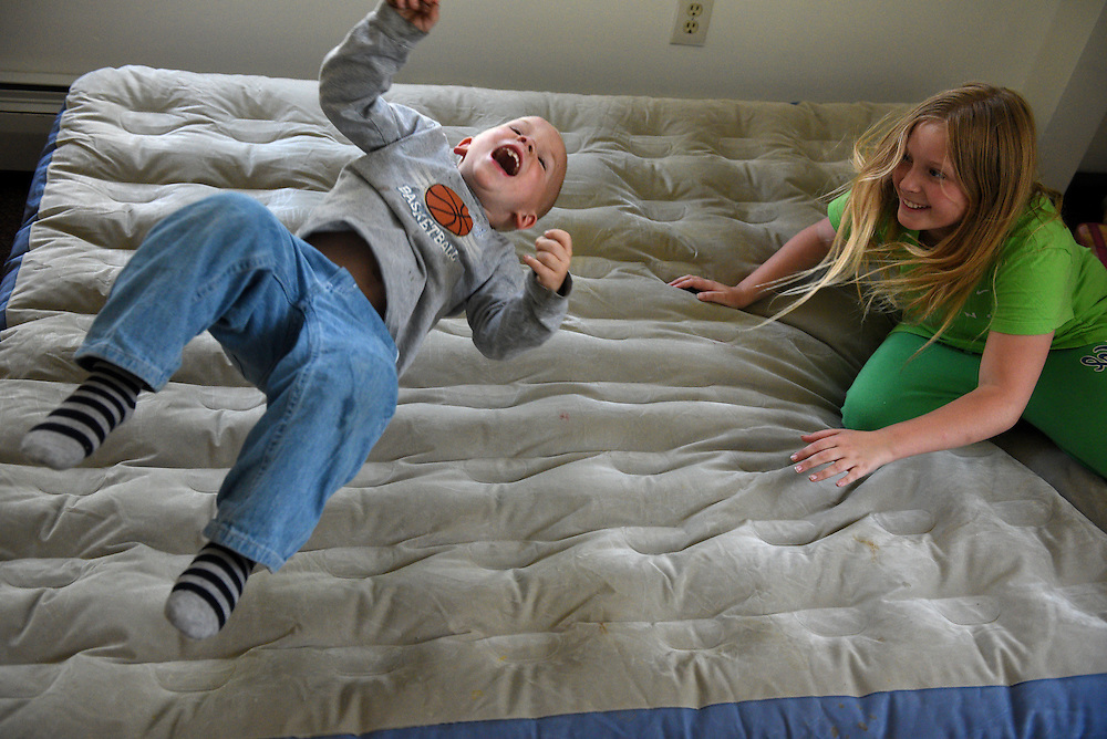 Brodee Davis, 3, shoots in the air after his sister Melanie Otten, 9, flops down on an air mattress in her bedroom on their first day in a new apartment in Claremont, N.H. Thursday, June 4, 2015. Davis and Otten had been living with their parents Marsha Barger Alexander and Elijah Alexander in Claremont's homeless shelter and the family was given housewares and clothing by the aid organization Baby Steps on their move-in day. (Valley News - James M. Patterson)<br /> Copyright © Valley News. May not be reprinted or used online without permission. Send requests to permission@vnews.com.