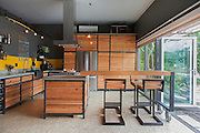 Jen and Bryn Scott of Zen Box Design are the proud designers and owners of 460 square feet with a Nanawall folding glass wall, DIY rolling doors, a wood counter that rolls out into a table, concrete coutner tops, a four burner gas stove, a two pot dish washer, various reclaimed wood (mostly Fir) cabinets, oriented strand board floors, a gas fireplace and a spcasious conrete bathroom with a sky light.<br /> Image by Shauna Intelisano