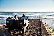 Couple sat in a landrover on the slipway at St Ouen's Bay, Jersey, CI, watching the surf with their surfboards in the back of the van.