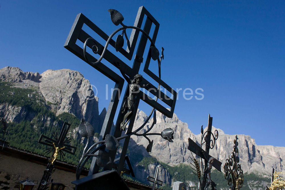 Iron crosses in the gothic churchyard of Colfosco, south Tyrol, Italy which dates back to the year 1420. The gothic church of Colfosco dates back to the year 1420. Colfosco, situated at 1,645 m asl, is the highest located village of Alta Badia. South Tyrol is a very religious and traditional country. The weekly walk to Mass and the celebration of religious festivals and processions are part of the culture and tradition in South Tyrol. In almost every house you will find a cross on a corner with consecrated palm branches over there. Also in the stable there are consecrated palm branches to keep away every disaster. South Tyroleans are almost all Catholics and quite conservative.