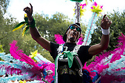 Notting Hill Carnival 2016 Childrens Day. A man in a costume decorated with feathers takes part in the carnival parade.