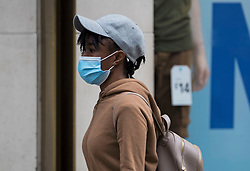 © Licensed to London News Pictures. 24/07/2020. London, UK. A shoppers wearing a mask on Oxford Street in central London, on the day that the wearing of mask in shops becomes compulsory. The UK Government has published formal guidance on spaces where the wearing of masks will now be mandatory, including in shops, supermarkets and shopping centres. Photo credit: Ben Cawthra/LNP