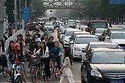 Masses of shared bikes mix with cyclists on their own bikes, motorbikes, electric vehicles and petrol driven cars during the evening rush hour. Downtown, Beijing China