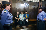 17/08/2012, Moscow, Russia..Maria Alyokhina, Yekaterina Samutsevich and Nadezhda Tolokonnikova of punk band Pussy Riot holding their trial verdicts inside the courtroom's glass cage after being sentenced to two years in prison for their performance in the Christ The Saviour Cathedral.