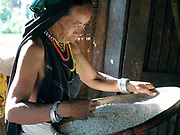 A Kayah ethnic minority woman wearing her traditonal clothing prepares rice at home in the  village of Kle Du in Kayah State, Myanmar on 20th November 2016