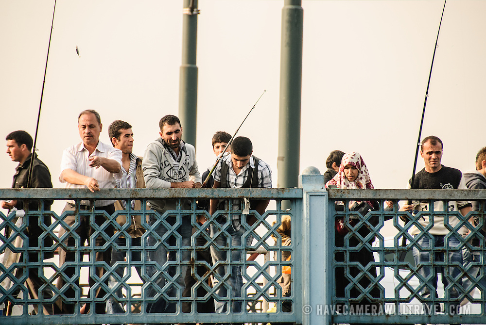 Fishing off Istanbul's historic Galata Bridge spanning the Golden Horn.