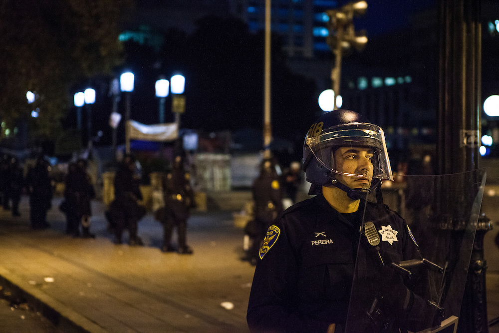 OAKLAND, CA - NOVEMBER 14, 2011: A San Francisco Police officer stands guard in front of Frank H. Ogawa Plaza as the Occupy Oakland encampment is broken down. Officers from multiple agencies were called in to support the OPD.