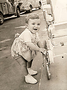 toddler standing by stroller France ca 1950s