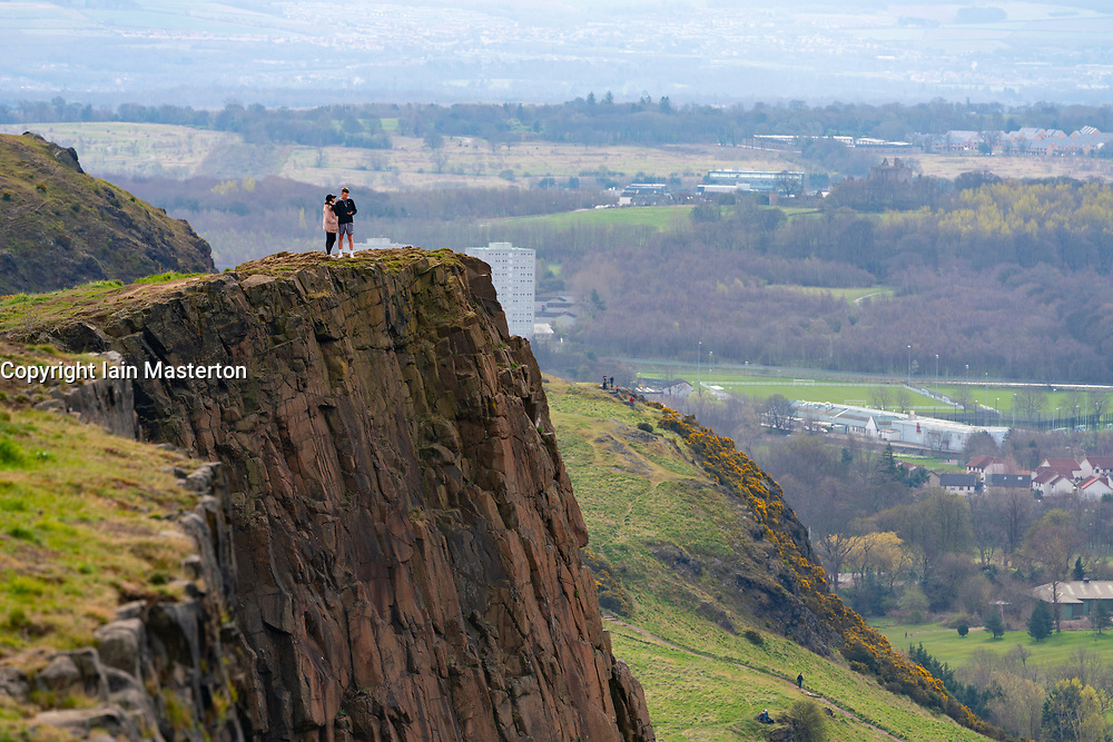 Edinburgh, Scotland, UK. 5 April, 2020. On the second Sunday of the coronavirus lockdown in the UK the public are outside taking their daily exercise. A couple out walking stand on cliff edge on Salisbury Crags in Holyrood Park. Iain Masterton/Alamy Live News