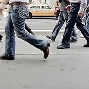 Legs of people walking in the street.