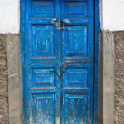 A old blue door set in adobe in Vaqueria, Peru along the Santa Cruz trek in the Andes Mountains in the Cordillera Blanca. 8.14.11