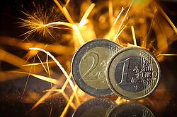 THEMENBILD - Euromuenze. Eine 2 Euro Muenze sowie eine 1 Euro Muenze stehen im Funkenschlag einer Wunderkerze. Aufgenommen am 16/11/2011 in Knittelfeld. EXPA Pictures © 2011, PhotoCredit: EXPA/ S. Zangrando