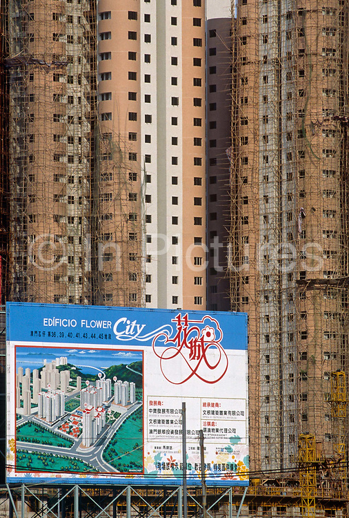 A new housing development of apartments in former Portuguese colony of Macau, now part of China. An artist's impression of the finished project is replicated on a board with the Portuguese word Edificio followed by the English Flower City, a sign of the times. Portuguese traders first settled in Macau in the 16th century and subsequently administered the region until the handover on 20 December 1999. Macau is now administered by China as a Special Economic Region (SER) and is home to a population of mainland 95% Chinese, primarily Cantonese, Fujianese as well as some Hakka, Shanghainese and overseas Chinese immigrants from Southeast Asia and elsewhere. The remainder are of Portuguese or mixed Chinese-Portuguese ancestry, the so-called Macanese, as well as several thousand Filipino and Thai nationals. The official languages are Portuguese and Chinese.