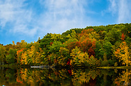 A lake in Appleton, ME ablaze with a refflection of trees in full Autumn color.