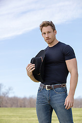 hot cowboy outdoors holding his hat