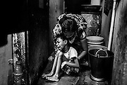 Lata Demade, 34, a '1984 Gas Survivor', is about to lift her daughter Mahima, 10, a girl affected by severe cerebral palsy, while in their bathroom in Navjeevan, one of the water-affected colonies in Bhopal, Madhya Pradesh, central India, near the abandoned Union Carbide (now DOW Chemical) industrial complex.