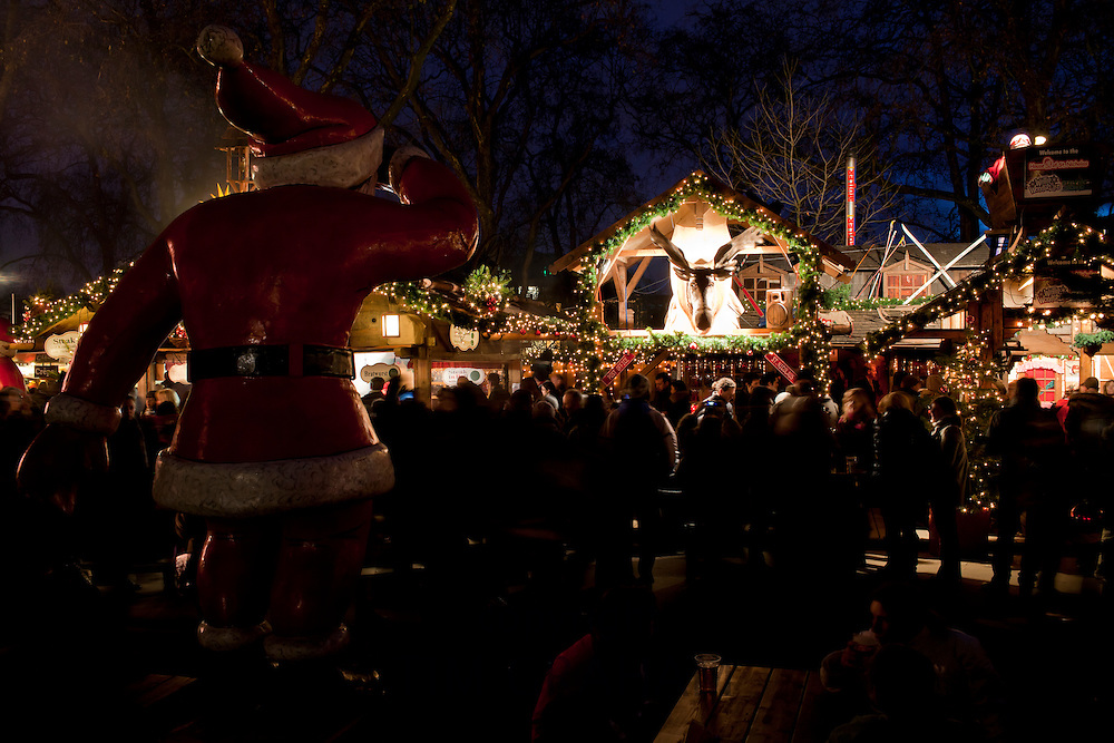 Father Christmas statue overlooks crowd at Christmas market, Winter Wonderland, in Hyde Park, London