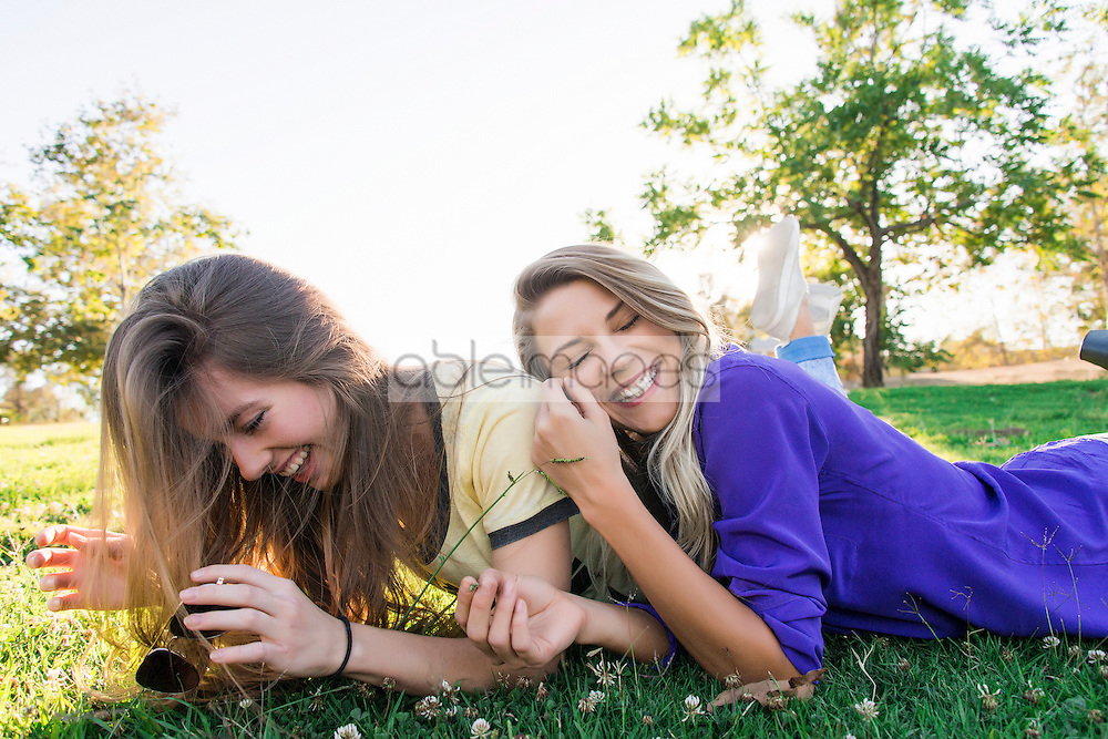 Two Women Lying on Grass Smiling