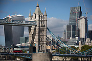A red London bus crosses Tower Bridge with construction work in progress in the capital's financial district (aka The Square Mile) behind, on 5th October, 2017, in London, England.