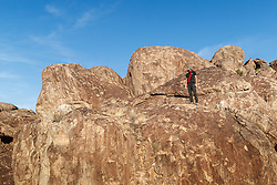 Climber on top of ledge after climbing large cliff face, Hueco Tanks State Park & Historic Site, El Paso, Texas. USA.