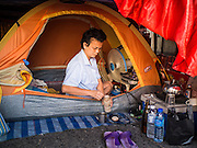 18 JANUARY 2015 - BANGKOK, THAILAND: A performer with the Sai Yong Hong Opera Troupe makes instant coffee in her tent beneath the stage at the Chaomae Thapthim Shrine, a Chinese shrine in a working class neighborhood of Bangkok near the Chulalongkorn University campus. The troupe's nine night performance at the shrine is an annual tradition and is the start of the Lunar New Year celebrations in the neighborhood. The performance is the shrine's way of thanking the Gods for making the year that is ending a successful one. Lunar New Year, also called Chinese New Year, is officially February 19 this year. Teochew opera is a form of Chinese opera that is popular in Thailand and Malaysia.             PHOTO BY JACK KURTZ