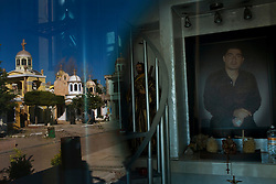 """A photo of a deceased man is seen through the door of his memorial chapel, as the rest of the cematary is reflected in the door. Large chapels are built in the cematary in Culiacan, Mexico, known locally as the """"Pantheon"""".  Some of the chapels, where the dead are buried, are two-story buildings complete with electricity and air conditioning.  This phenomenon, where people build increasingly large, luxurious memorials to their dead family members, is often associated with Mexico's Narco Culture."""