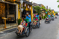 Tourists peddled through the Old Town on Cyclos (three wheeled bicycle taxis), Hoi An, Vietnam.
