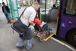 Young woman with Cerebral Palsy in a wheelchair and her boyfriend getting on a bus using a mobility ramp,