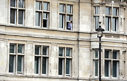 © Licensed to London News Pictures. 09/05/2012. Westminster, UK A man watches from an office window. The procession carrying Queen Elizabeth II on its way to the Palace of Westminster today 9th May 2012. It is the first Queen's Speech, the grandest event on the parliamentary calendar, since shortly after the coalition Government was formed. The statement usually takes place each autumn. Photo credit : Stephen Simpson/LNP
