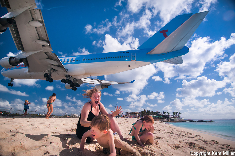 """Jessie Miller and her children, Jamie, 5, left, and Betsy, 8, of Bay City, Mich. react to the thunderous 747 jumbo jet as it passes within 60 feet above land. As the plane flew over, the sand kicked up and blasted the Miller's bare skin.  """"Ahhhhhhhhhh!"""" the three screamed, as they ran away from the sand and noise. """"It was exhilarating,"""" Miller said.<br /> <br /> The Princess Juliana International Airport in St. Maarten is famous for its short runway. At only 7,980 ft, it is barely long enough for large jets to land. Incoming airplanes approaching the island, must touchdown at the very beginning of the runway. This means they have to fly extremely low, passing only 30-60 feet over tourists on Maho beach. <br /> <br /> In early 2000, pictures of low flying aircraft were published in several news magazines. The photos looked so unreal that some were disputed as fakes. Plane spotters come from all over the world to witness the thrilling approaches and take-offs.<br /> <br /> The Paris based French carrier Corsair is the only airline to operate a 747 at the airport. It does so twice a week during peak season.<br /> <br /> Despite the difficulties in approach, there have been no major incidents at the airport."""