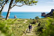 Children holding buckets and spades, running down the grassy path leading to the calm, blue sea at beautiful Beauport Beach, a hidden cove on the south coast of Jersey, Channel Islands