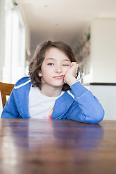 Portrait of girl sitting at wooden table