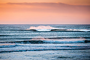 Pink spray bouncing off the waves at sunset at St Ouen's Bay, Jersey, CI
