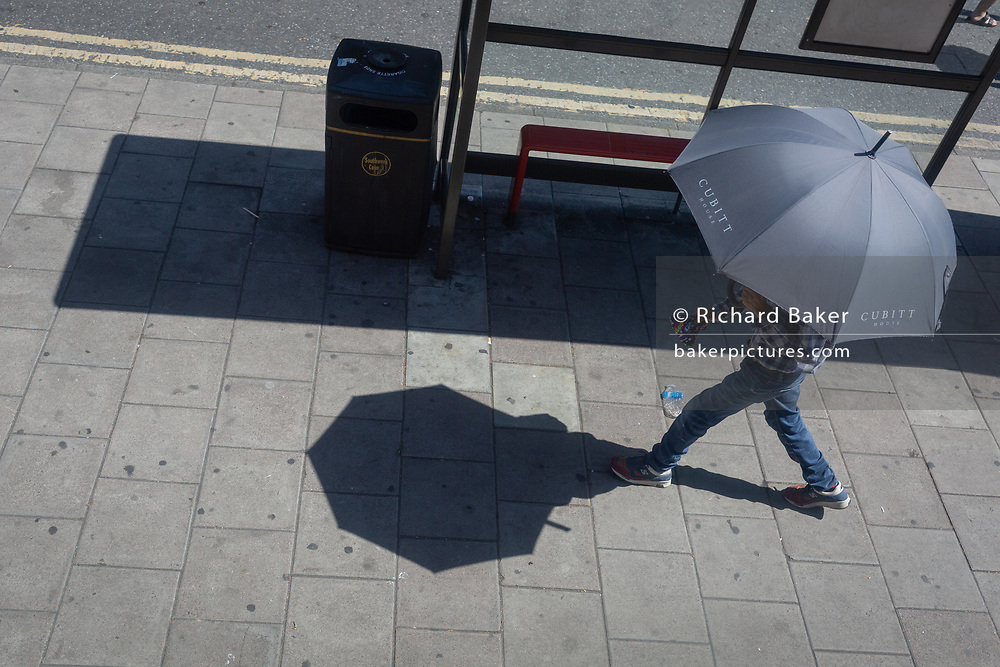 On the hottest day of the year so far in 2020 when temperatures in central London  reached 37 degrees Celcius, a man walks past a bus shelter in Camberwell and during the Coronavirus pandemic, on 31st July 2020, in London, England.