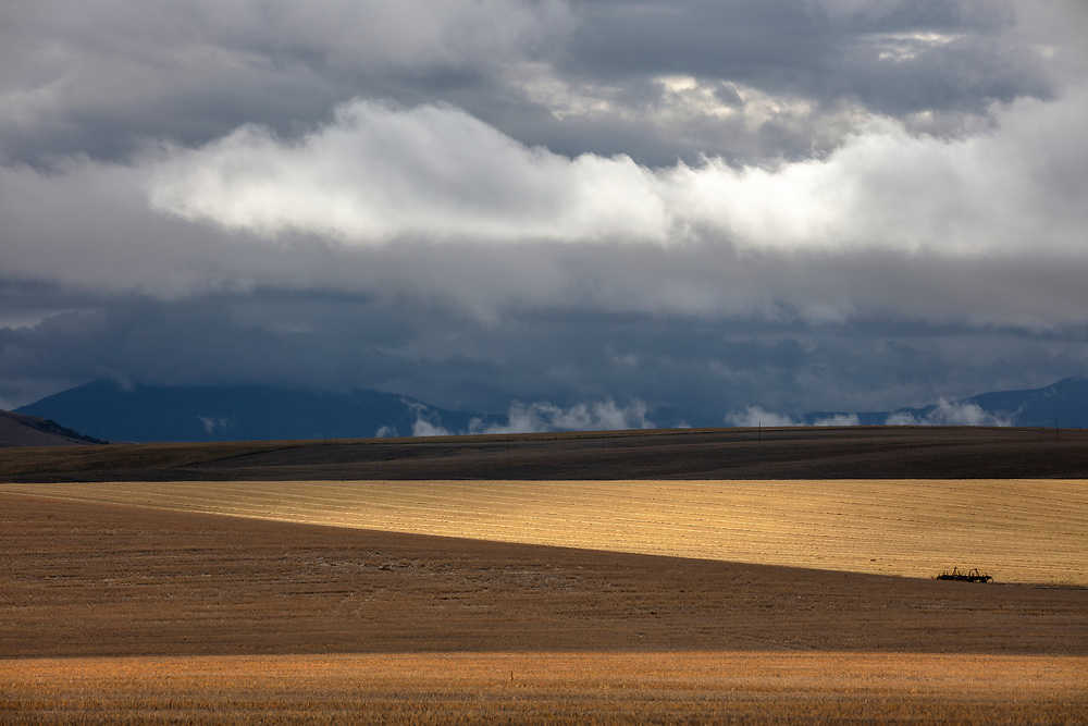 Storm clouds and Montana agriculture land in early dormant springtime