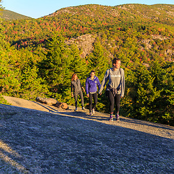 """Three women hiking on """"The Beehive"""" in fall in Maine's Acadia National Park.`"""