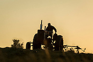Goshen, New York - A farmer on a tractor uses a hay tedder in a field on June 9, 2016.